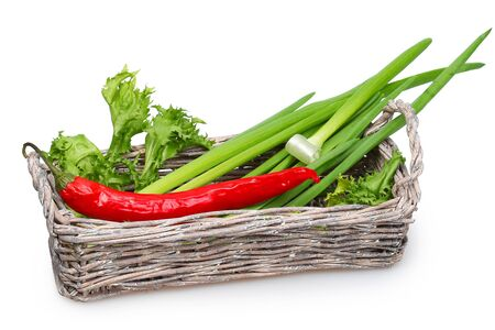 pungent: Old wicker basket with green onions, fresh lettuce and pungent red pepper Stock Photo