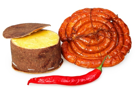 Packaged cheese, smoked sausage and red pepper pod of dark on a white background photo