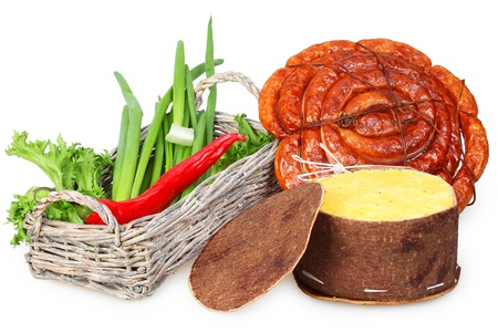 Wicker basket with green and red peppers, smoked sausage and cheese in the Hungarian packaging made of birch bark photo
