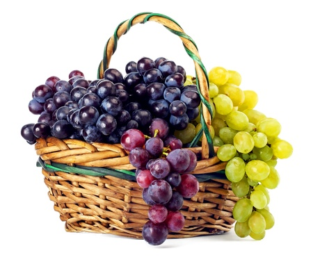 Clusters of yellow and black grapes in a basket on a white background photo