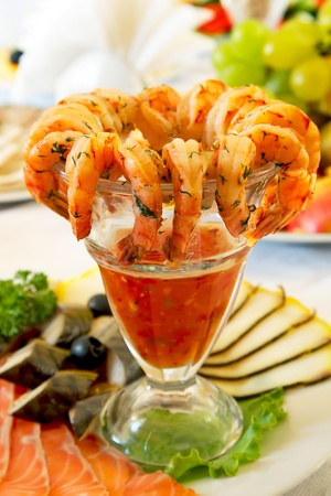 Vase with tiger prawns and sauce, table photo