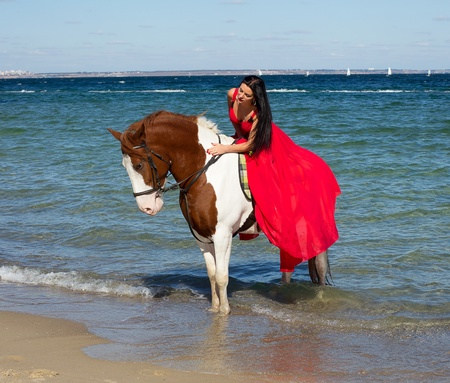 A young girl in a red dress on a horse, sea coast on a summer day Stock Photo