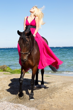A horse with a girl in a red dress, the sea coast in the summer sun denden Stock Photo