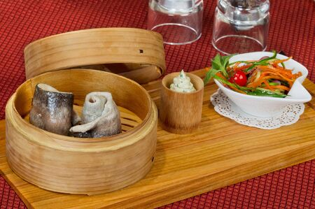 Fresh trout in a wooden bowl, steamed, is on red napkin. Fresh vegetable salad in a white bowl. photo