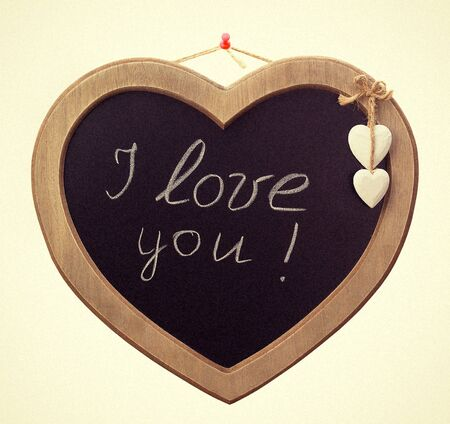 Wooden board for notes in a heart shape with the words white chalk I love you photo