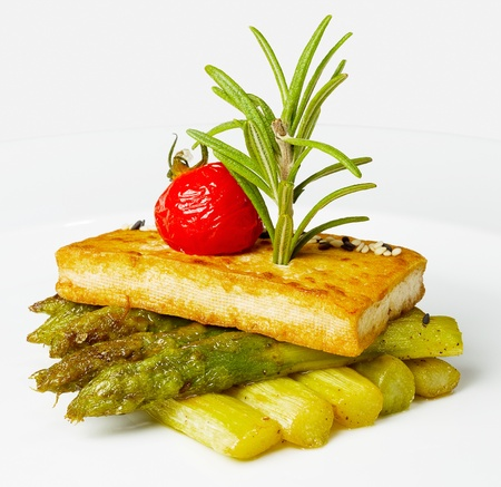croutons: Asparagus with croutons, pickled tomatoes and sesame seeds on a white plate. Creative Food