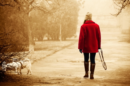 Girl in a bright red coat walking in the park with a dog on a cloudy autumn day. Sepia. photo