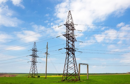 high-voltage power lines in a field on a summer day photo