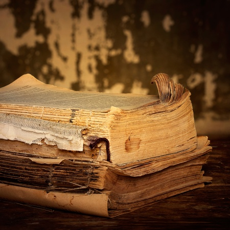 decrepitude: Old books of the Old binder are stacked on a wooden surface Stock Photo