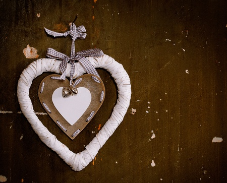 Decorative heart bauble hanging from a nail on the old wall photo