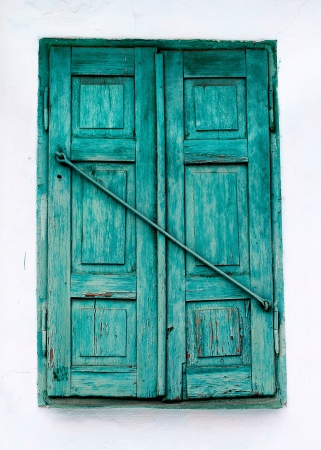 Old rustic window closed wooden shutters painted with green paint photo