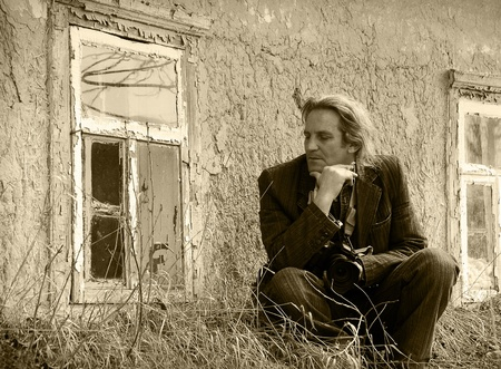 Sad middle-aged man sitting in front of an abandoned house  Vintage photo