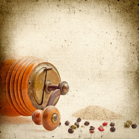Old Pepper grinder mill with different dried peppers. Vintage paper grunge, for any of your project photo