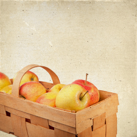 Ripe apples in a wicker basket  Vintage background with texture of paper, for any of your design photo