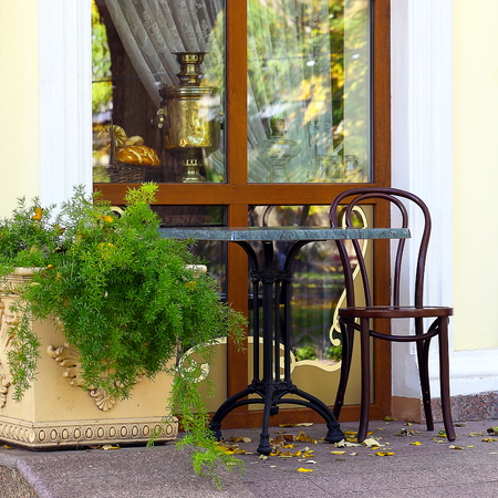 A lone table and chair in the autumn cafe  Happy on the street  photo