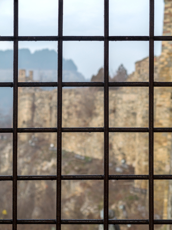 Brick fortress seen through the prison window with metal bars photo