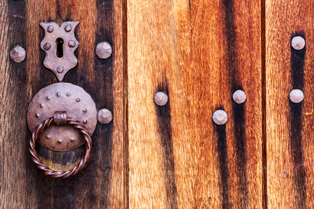 Textured wooden door of an abandoned barn with a metal lock and handle  photo