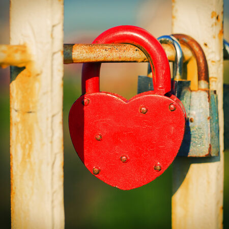 concomitant: Red metal lock Key from heart of love, vintage background