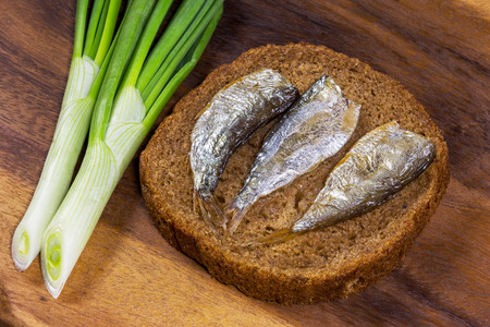 Rye bread with delicious anchovies on old wooden table photo
