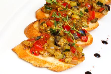 Bruschetta (Italian Toasted Garlic Bread) with stewed vegetables, selective focus. Creative cuisine. photo