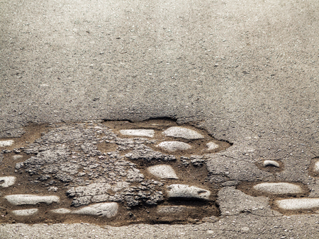 gully: Cutting of an old road with cracked asphalt and a gully in the center of cobblestones Stock Photo