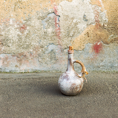 oldness: Old ceramic jug on a road near the oldness of the rough wall