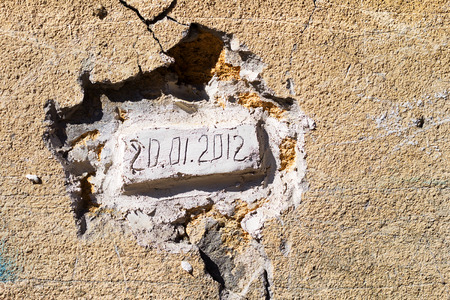 requires: Bricks laid in an old wall with the date of the bookmark. Dirty concrete wall with cracks and scratches. Requires urgent repairs. Grungy concrete surface. Great background or texture for your project.