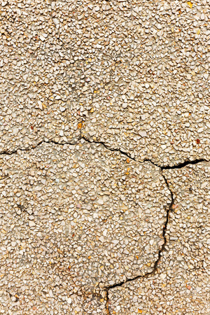 small stones: Concrete with small stones, cracks and scratches, weathered, worn. Grunge Concrete Surface. Great background or texture.