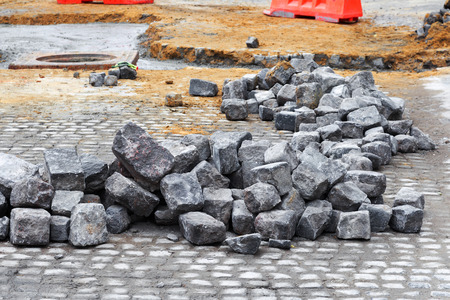 materials: Pieces of rubble lying on the road, there is repair construction work