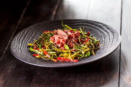 Authentic salad with bacon fresh red pepper, sprouts, sesame and olive oil on a black plate. Morning atmospheric lighting, fashionable trendy spot soft focus. Preparation for design creative menu. photo