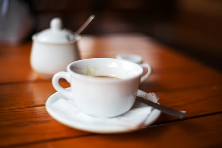 Stil: Cup of coffee. Morning atmospheric lighting, fashionable trendy spot soft focus. Preparation for design creative menu. Stock Photo