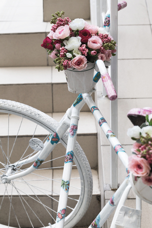 original bike: Creative bouquet of colorful artificial flowers on old white bicycle, retro. Selective focus and space in the zone blurring compositions for the production of advertising and text.