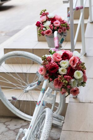 original bike: Creative bouquet of colorful artificial flowers on old white bicycle. Selective focus and space in the zone blurring compositions for the production of advertising and text.