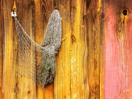redes de pesca: Old fishing nets hang on the painted wooden wall of a barn