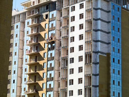 fillers: ODESSA - SEPTEMBER 12: facade thermal insulation works with stopping and fillers during the construction of high-rise apartment building September 12, 2015 in Odessa, Ukraine.
