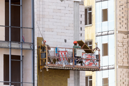 fillers: ODESSA - SEPTEMBER 8: facade thermal insulation works with stopping and fillers during the construction of high-rise apartment building September 8, 2015 in Odessa, Ukraine.