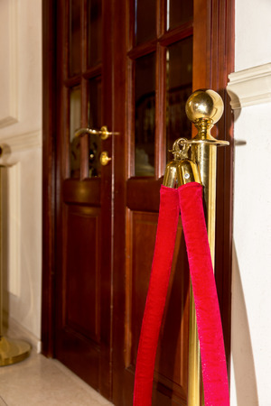stanchion: Red barrier rope on wooden door background. Selective focus. event object