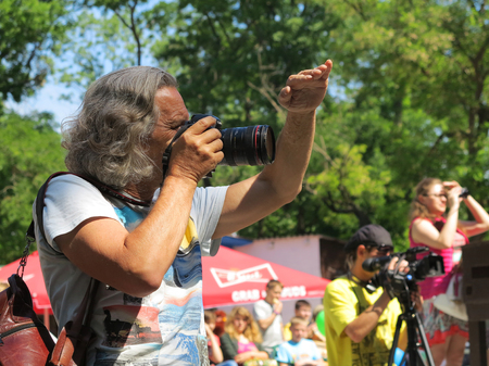 press agent: ODESSA - MAY 30, 2015: The gray-haired tanned male photographer at work in the park, sunny day May 30, 2015 in Odessa, Ukraine
