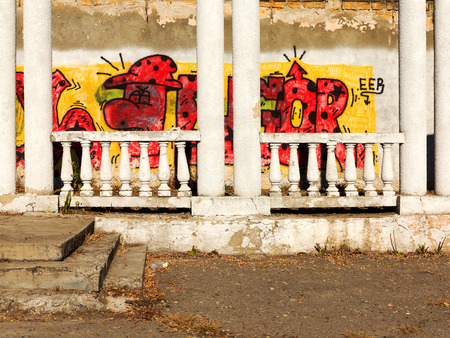 bullies: ODESSA - NOVEMBER 1: Old abandoned building with columns, graffiti on a wall. Grungy concrete surface with cracks, scratches and streaks of paint. November 1, 2015 in Odessa, Ukraine
