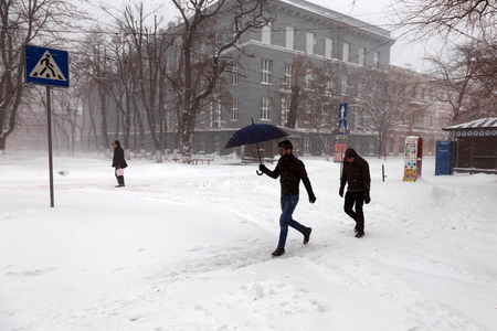 ODESSA - January 18, 2016: On snow-covered street. People go along the street during a snowfall. January 18, 2016 in Odessa, Ukraine Editorial