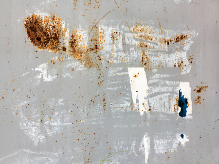 antique background: Creative background of rusty metal, painted gray paint carelessly with the remnants of torn paper.