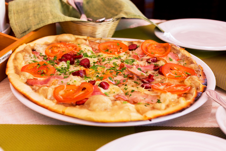 showcase interior: Authentic pizza with tomatoes, smoked sausage, bacon and parsley. Stock Photo