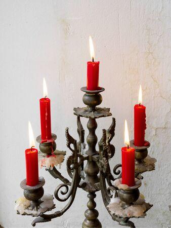 오래 된 벽의 배경에 빨간색 촛불와 레트로 촛대