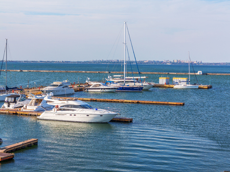 to depart: Odessa, Ukraine July 6, 2016: Yacht Club with parked vehicles of various models. Pleasure boat with tourists depart from the pier in Odessa, Ukraine, July 6, 2016 Editorial