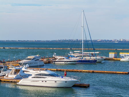 Odessa, Ukraine July 6, 2016: Yacht Club with parked vehicles of various models. Pleasure boat with tourists depart from the pier in Odessa, Ukraine, July 6, 2016 Editorial