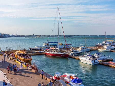 private club: Odessa, Ukraine July 6, 2016: Yacht Club with parked vehicles of various models. Pleasure boat with tourists depart from the pier in Odessa, Ukraine, July 6, 2016 Editorial