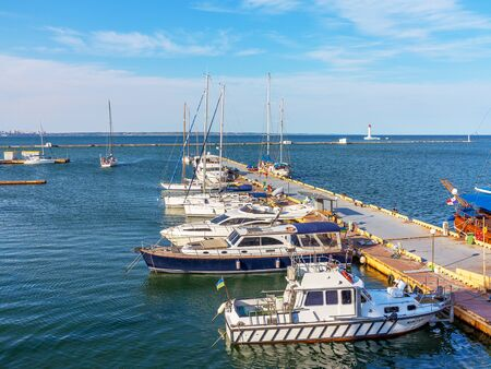 cruising: Odessa, Ukraine July 6, 2016: Yacht Club with parked vehicles of various models. Pleasure boat with tourists depart from the pier in Odessa, Ukraine, July 6, 2016 Editorial