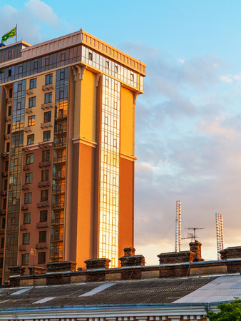 tall chimney: Odessa, Ukraine July 6, 2016: The old roofs on a background of a modern high-rise building, the sunset at the end of the day in Odessa, Ukraine, July 6, 2016 Editorial
