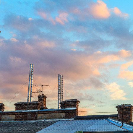 tall chimney: The old roof of the house, the sunset at the end of the day
