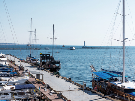 Odessa, Ukraine August 15, 2016: Yacht Club with parked vehicles of various models. Pleasure boat with tourists depart from the pier in Odessa, Ukraine, August 15, 2016 Editorial